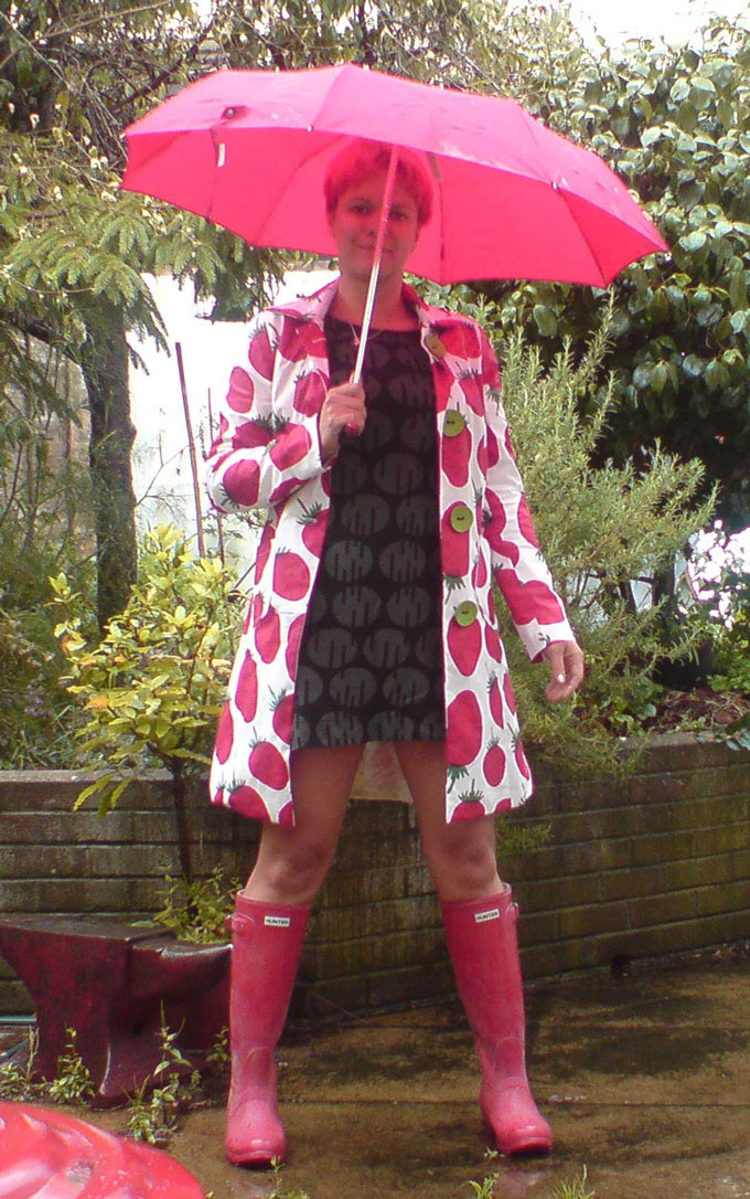 Bess standing in strawberry print Marimekko raincoat