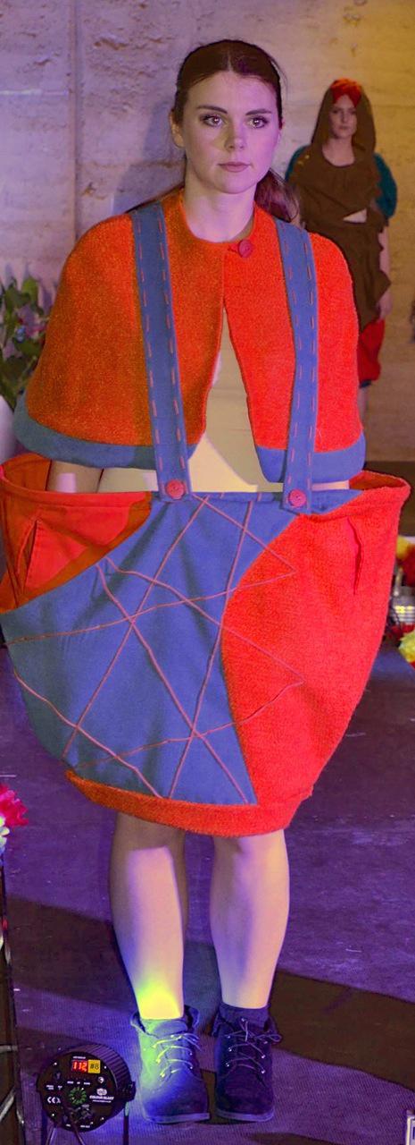 catwalk show of orange bouclé knit braced skirt