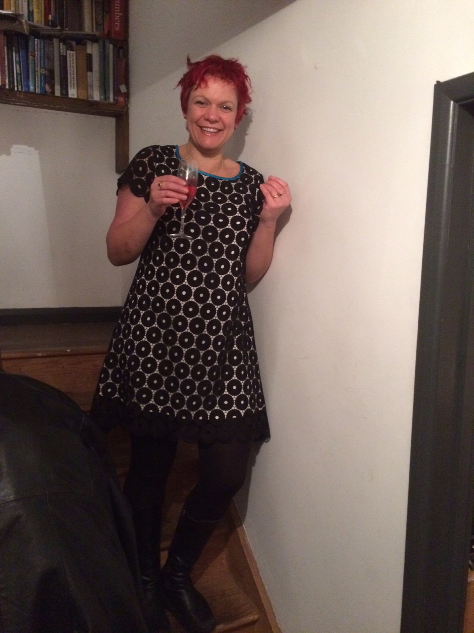 Bess wearing black circles lace dress holding a glass of bubbly