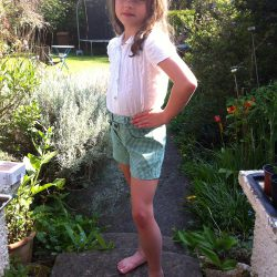 white spotty jacquard cotton school shirt and green gingham shorts