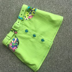 kid's lime green stretch denim mini skirt with matching belt and floral contrast pockets