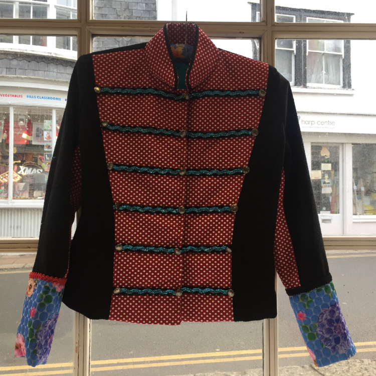 Front view hotchpotch military style jacket using black piqué weave wool, red and white polka dot brocade, multicolour floral print brocade, sequinned rickrack, military buttons and gimp braids