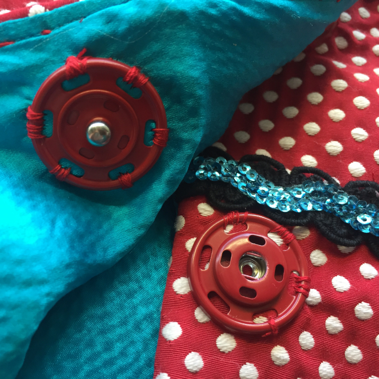 Jacket detail: Giant red sew on snap fastener, electric blue turquoise silk seersucker satin, sequinned rickrack and gimp braid.