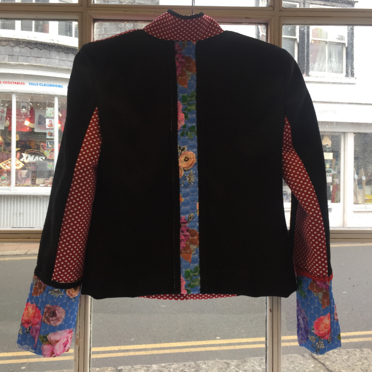 Back view hotchpotch military style jacket using black piqué weave wool, red and white polka dot brocade, multicolour floral print brocade