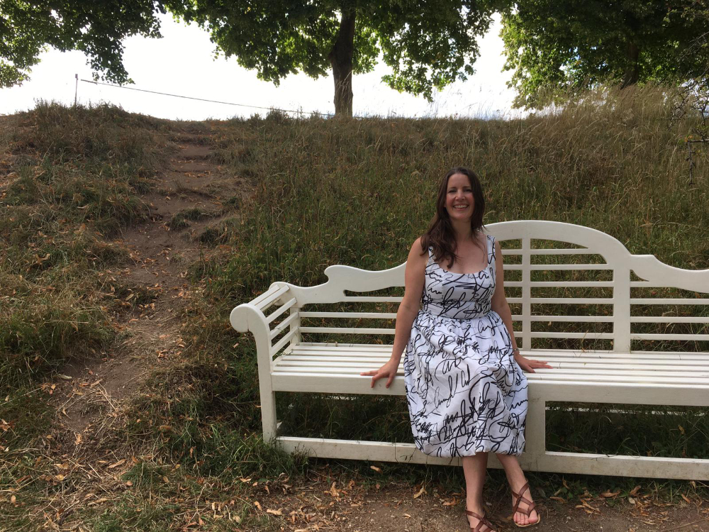catharine sitting on wooden bench wearing cotton voile monochrome scribble print dress
