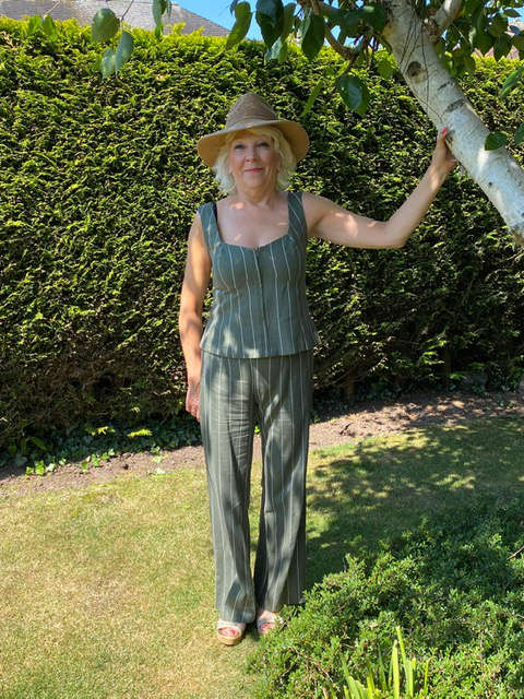 Paula stood under tree in garden wearing olive stripe linen matching trousers and top