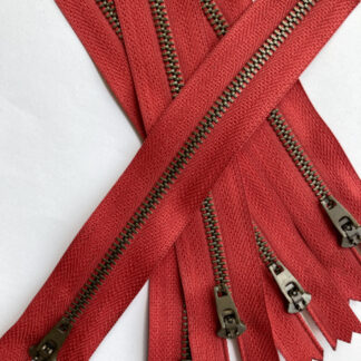 Red tape with antique brass metal teeth jeans zip